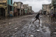 "In this photo released by UNICEF, a woman crosses the street on a flood effected road as hurricane Matthew passes over on October 4, 2016 Port au Prince. Weakened but still dangerous, Hurricane Matthew churned toward the Bahamas Wednesday en route to an already jittery Florida after killing at least nine people in the Caribbean in a maelstrom of wind, mud and water. / AFP PHOTO / UNICEF / Logan ABASSI / RESTRICTED TO EDITORIAL USE - MANDATORY CREDIT ""AFP PHOTO / UNICEF/ Logan ABASSI - NO MARKETING - NO ADVERTISING CAMPAIGNS - DISTRIBUTED AS A SERVICE TO CLIENTS"